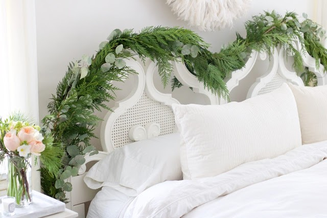 white juju hat over vintage white cane headboard with evergreen and eucalyptus garland, garden roses and pottery barn velvet pillows
