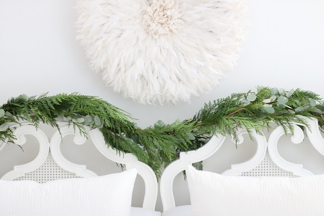 white juju hat over vintage white cane headboard with evergreen and eucalyptus garland and pottery barn velvet pillows